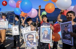 أطفال يطلقون بالونات تحمل صور شخصيات فلسطينية قرب حدود غزة