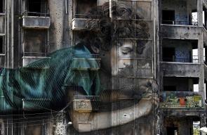 جدارية لطفل يعمل على جهاز الكتروني على مبنى متضرر خلال الحرب الأهلية في بيروت