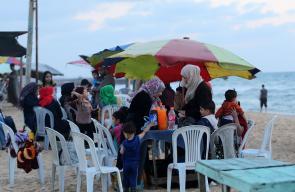 في ظل الأجواء الحارة وأزمة الكهرباء.. عائلات تفطر على شاطئ بحر غزة