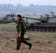 An-Israeli-soldier-walks-next-to-a-mobile-artillery-unit-positioned-outside-the-northern-Gaza-Strip