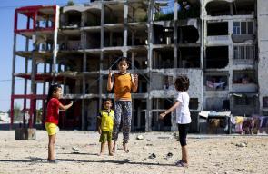 أطفال فلسطينيون يلعبون أمام بقايا أبراج الندى السكنية شمال القطاع
