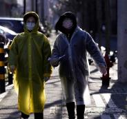 w1240-p16x9-Women wear face masks and plastic raincoats as a protection from coronavirus in Shanghai, China February 17, 2020. REUTERS OK